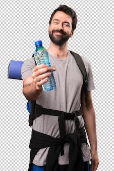 Glücklicher hübscher wanderer mit einer flasche wasser