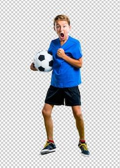 Glücklicher junge, der fußball spielt