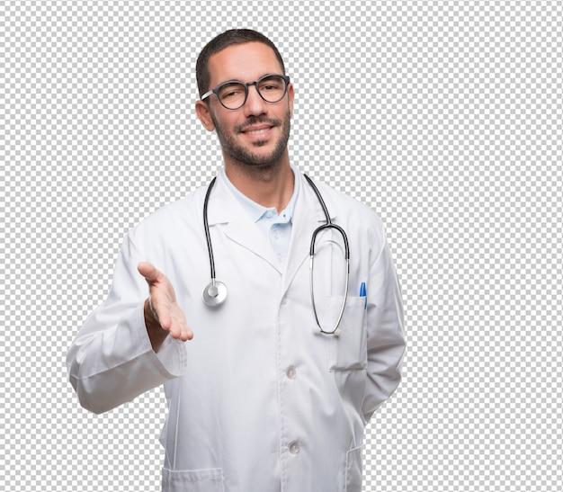 Glücklicher junger doktor, der eine händedruckgeste tut