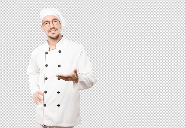 Glücklicher junger koch, der eine geste des willkommens mit seiner hand tut