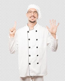Glücklicher junger koch, der eine geste nummer sechs mit seinen händen tut