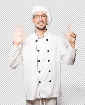 Glücklicher junger koch, der eine geste nummer sieben mit seinen händen tut
