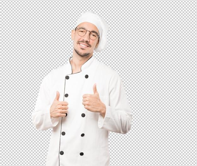 Glücklicher junger koch, der gestikuliert, dass alles in ordnung ist