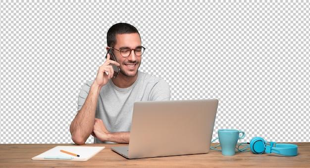 Glücklicher junger mann am telefon und sitzen an seinem schreibtisch