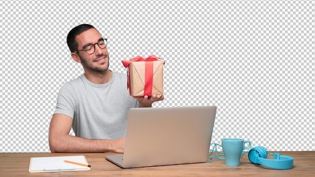Glücklicher junger mann, der an seinem schreibtisch sitzt und ein geschenk hält