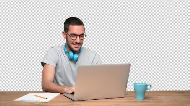 Glücklicher junger mann, der an seinem schreibtisch sitzt und kopfhörer verwendet