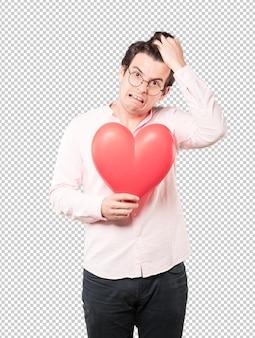 Glücklicher junger mann, der ein großes spielzeugherz hält und gesten über valentinstag tut
