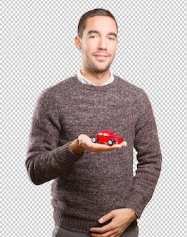 Glücklicher junger mann, der ein spielzeugauto hält