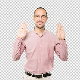 Glücklicher junger mann, der eine geste des stopps mit seiner handfläche macht