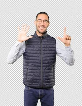 Glücklicher junger mann, der eine geste nummer sieben mit seinen händen tut