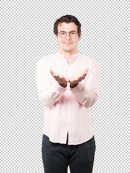 Glücklicher junger mann, der etwas mit seiner hand hält