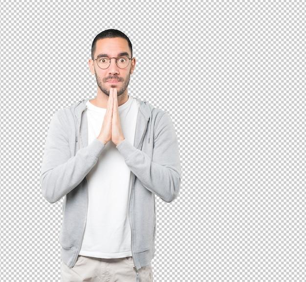 Glücklicher junger mann, der geste betet