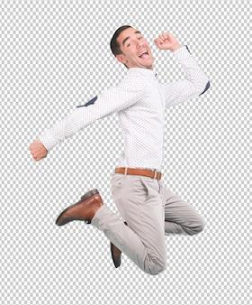 Glücklicher junger mann, der mit einer geste der feier - voller körperschuß springt