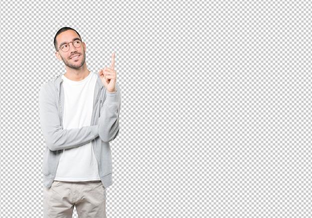 Glücklicher junger mann, der mit seinem finger nach oben zeigt