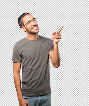 Glücklicher junger mann, der oben mit seinem finger zeigt