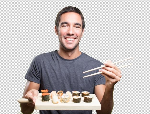 Glücklicher junger mann, der sushi isst