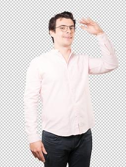 Glücklicher junger mann mit einer geste des wegsehens