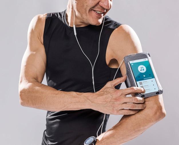 Glücklicher läufer mit smartphone-modell