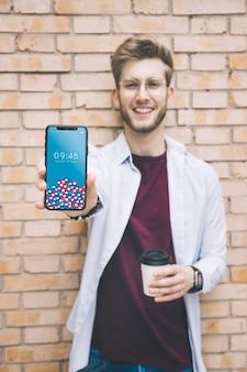 Glücklicher mann, der smartphone zeigt