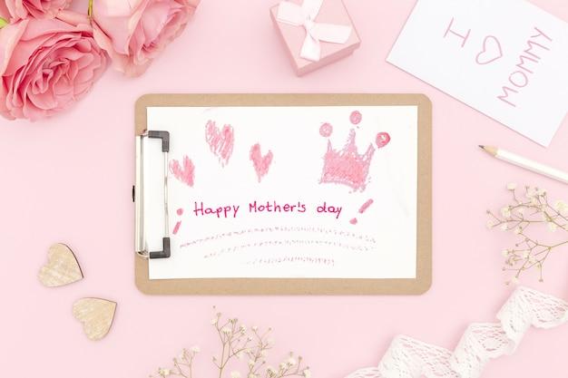 Glücklicher muttertagsnotizblock mit rosen und geschenk