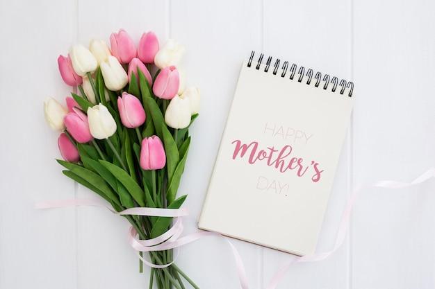 Glücklicher muttertagspott oben auf notizbuch mit den rosa und weißen tulpen, auf weißem hölzernem hintergrund