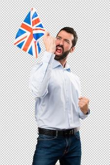Glücklicher stattlicher mann mit dem bart, der eine flagge vereinigten königreichs hält