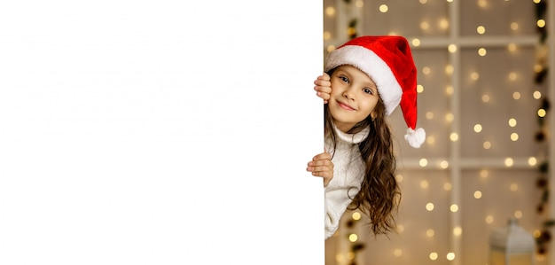 Glückliches kleines kindermädchen in der roten weihnachtsmannmütze, die weißen karton hält