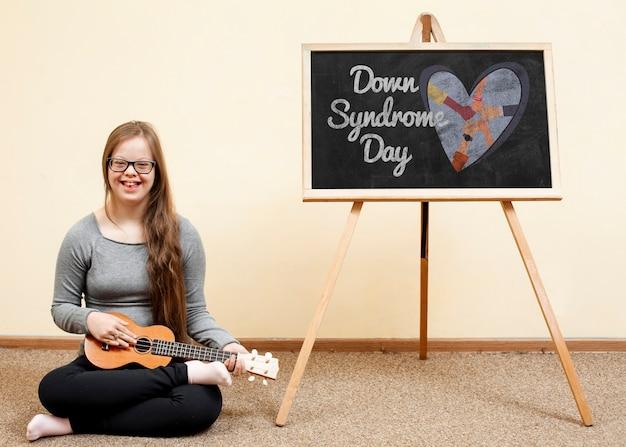 Glückliches mädchen mit down-syndrom spielt ukulele mit tafelmodell