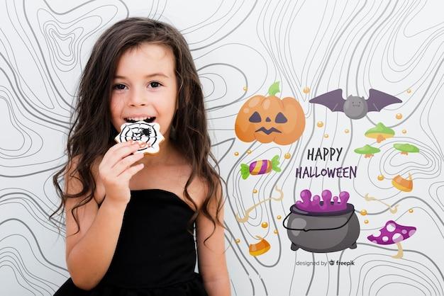 Glückliches nettes mädchen halloweens, das eine süßigkeit isst