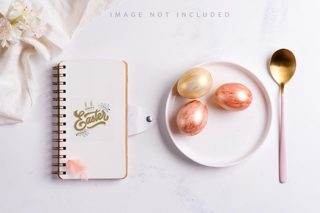 Glückwunschkarte mit leerem notizbuchmodell, handgemachte bemalte eier auf einem teller, goldener löffel