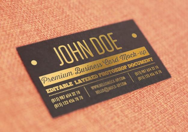 Goldbriefbeschwerer auf schwarzem papiervisitenkarteschablonenmodell auf textilart oberfläche