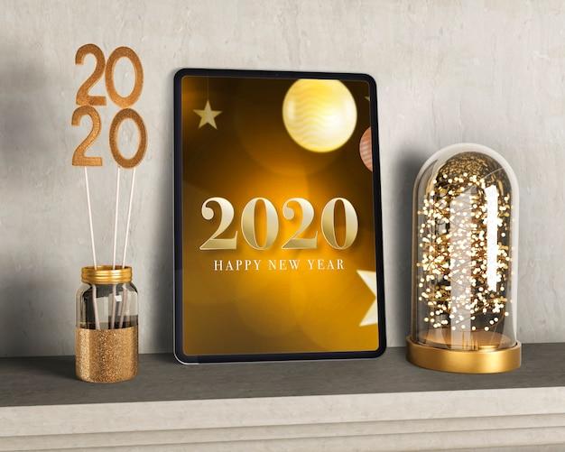 Goldene dekorationen neben tablette für neues jahr