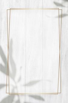 Goldener rahmen mit blätterschatten auf einfachem hölzernem beschaffenheitshintergrund