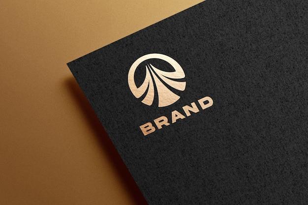 Goldenes logomodell auf schwarzem papier geprägt