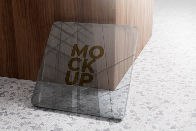 Goldlogo-modell auf glas auf hölzernem hintergrund