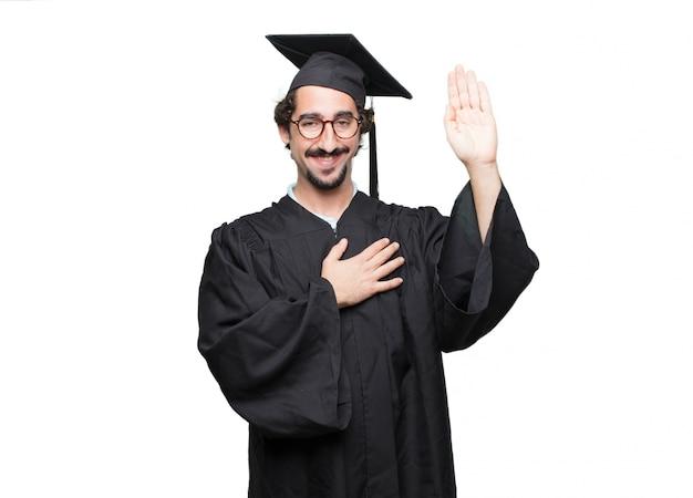 Graduate bärtiger mann lächelt selbstbewusst, während er ein aufrichtiges versprechen oder einen eid ablegt
