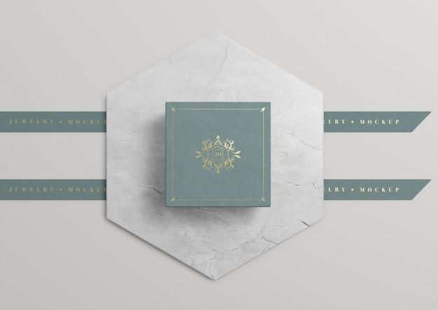 Grüne schmuckschatulle auf marmor mit goldenem symbol