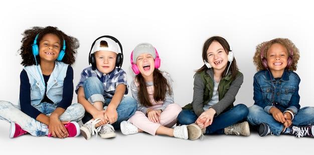 Gruppe kinderstudio-lächelnde tragende kopfhörer und winter-kleidung