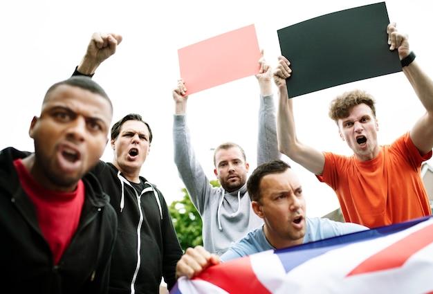 Gruppe wütende männer, die eine britische flagge und leere bretter während eines protests schreien zeigen