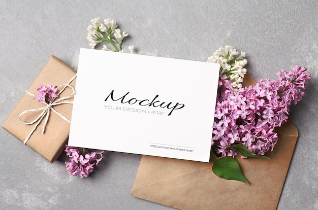 Gruß- oder einladungskartenmodell mit geschenkbox, umschlag und lila frühlingsblumen