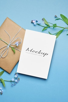 Grußkartenmodell mit geschenk und frühlings-vergissmeinnicht-blumen auf blau