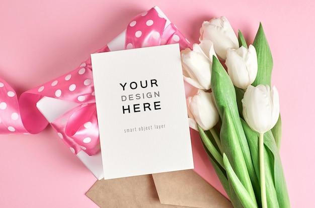 Grußkartenmodell mit geschenkbox und weißem tulpenblumenstrauß auf rosa