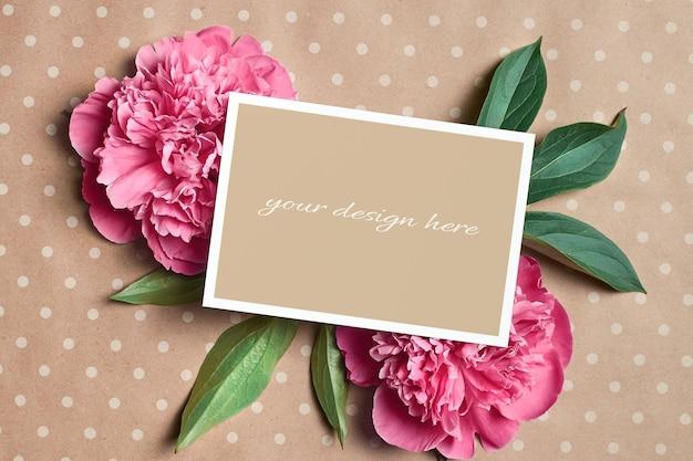 Grußkartenmodell mit rosa pfingstrosenblumen auf kraftpapierhintergrund