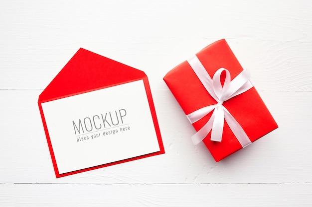 Grußkartenmodell mit rotem umschlag und geschenkbox auf weiß