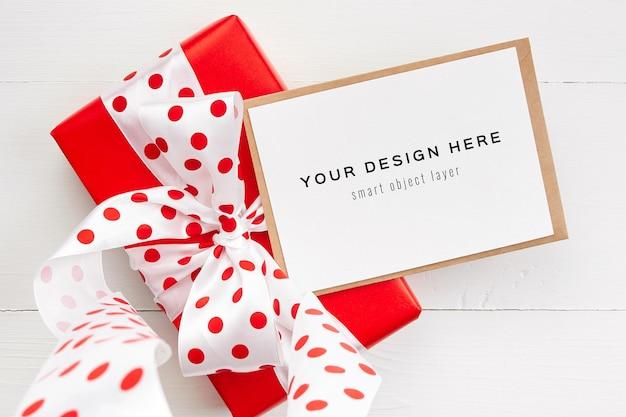 Grußkartenmodell mit roter geschenkbox mit schleife auf weißem hintergrund