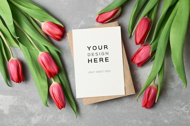 Grußkartenmodell mit umschlag und roten tulpenblumen