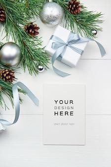 Grußkartenmodell mit weihnachtsdekorationen auf weißem hölzernem hintergrund