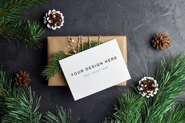 Grußkartenmodell mit weihnachtsgeschenkbox und tannenzweigen und -kegeln