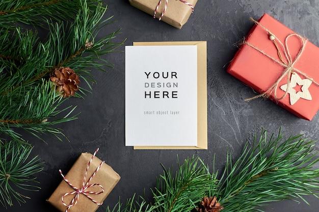 Grußkartenmodell mit weihnachtsgeschenkboxen und tannenzweigen und -kegeln auf dunkelheit
