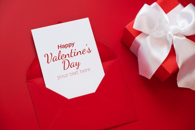 Grußkartenmodell, weiße leere karte im umschlag und geschenkbox auf rotem hintergrund.